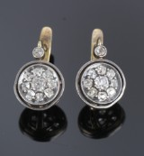 Pair of diamond rosette earrings, 18 kt. gold and silver, total approx. 1.40 ct. Late 19th century. (2)