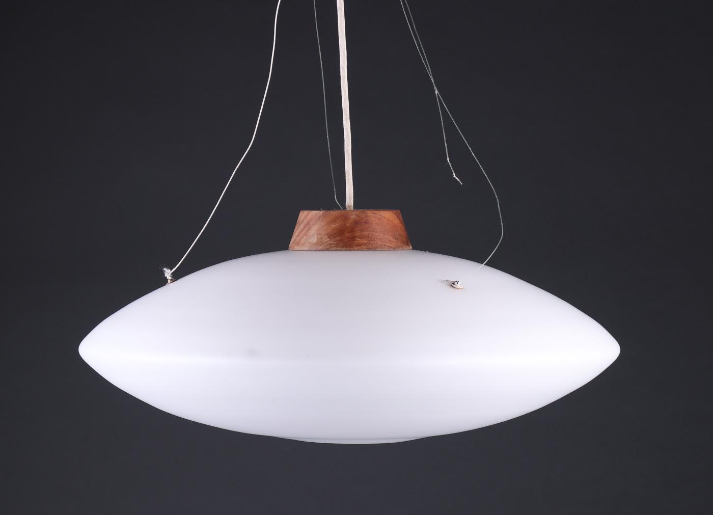 Pendel af opalglas og messing, 1960erne - Pendel af opalglas, top af teaktræ, ophængt i liner, Ø ca. 52 cm. 1960erne. Fremstår med brugsspor; ene ophængsbeslag mgl. tap
