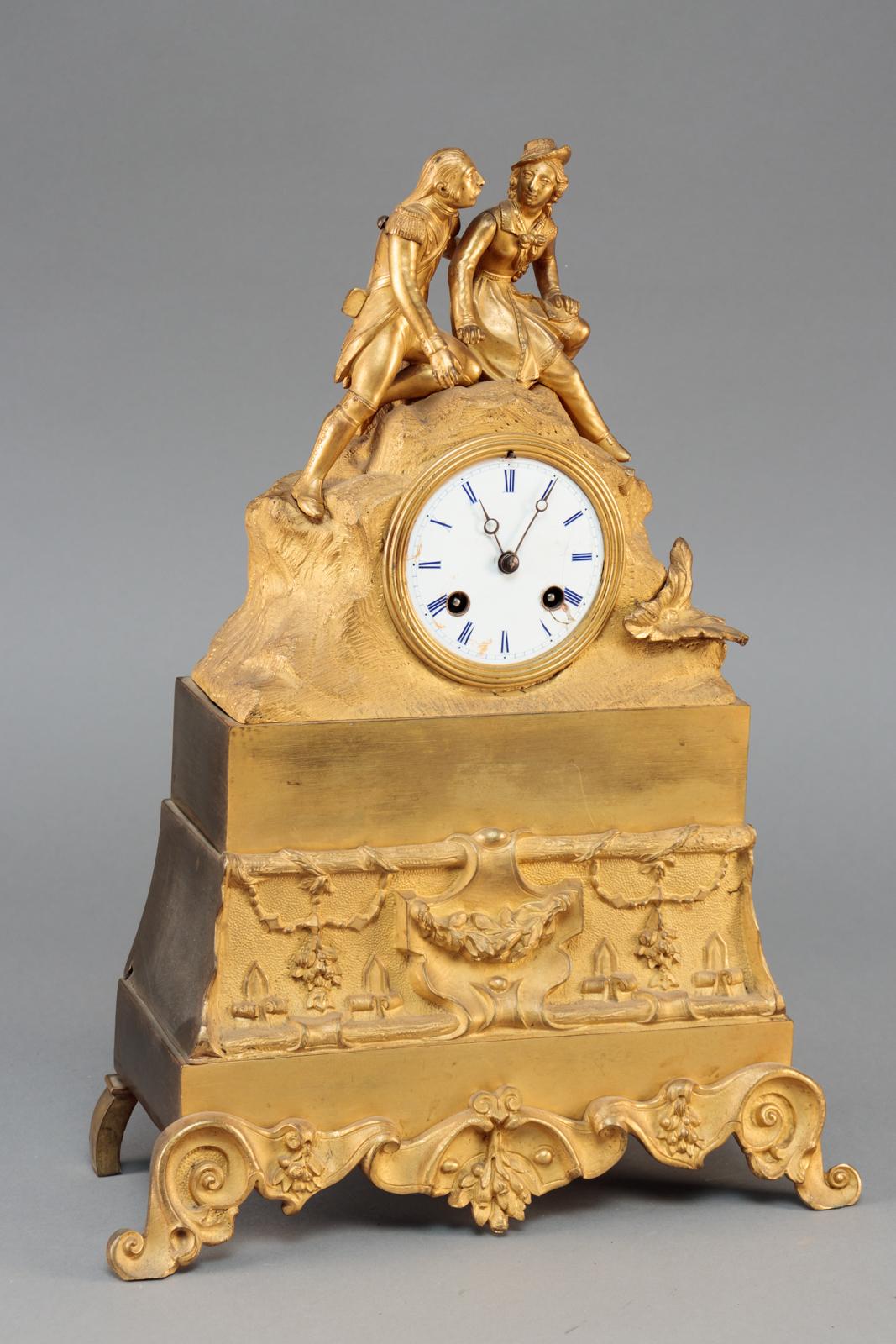 Napoleon III kaminur af forgyldt bronze, urhus med soldat og kvinde - Napoleon III kaminur af forgyldt bronze, urhus med soldat og kvinde, skive med romertal. Støbt med ornamentik, blomster og bladværk. Frankrig 19. årh.s anden halvdel. H. 39 cm. B. 29 cm. D. 11 cm. Pendul og optræksnøgle medfølger