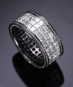 Brillantbesat herrering i 18 kt. sortrhodineret guld, 9.60 ct. - Dk, Vejle, Dandyvej - Bred herrering i 18 kt. sortrhodineret hvidguld prydet hele ringskinnen rundt med 96 prinsesseslebne diamanter i invisible setting på tilsammen ca. 9.60 ct. Farve: Wesselton (H), klarhed: VVS. Flankeret af små brillantslebne diaman - Dk, Vejle, Dandyvej