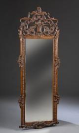 Spejl i ramme af udskåret egepoleret træ. Rokoko form.