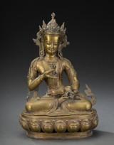 Buddha af bronze siddende på lotustrone.