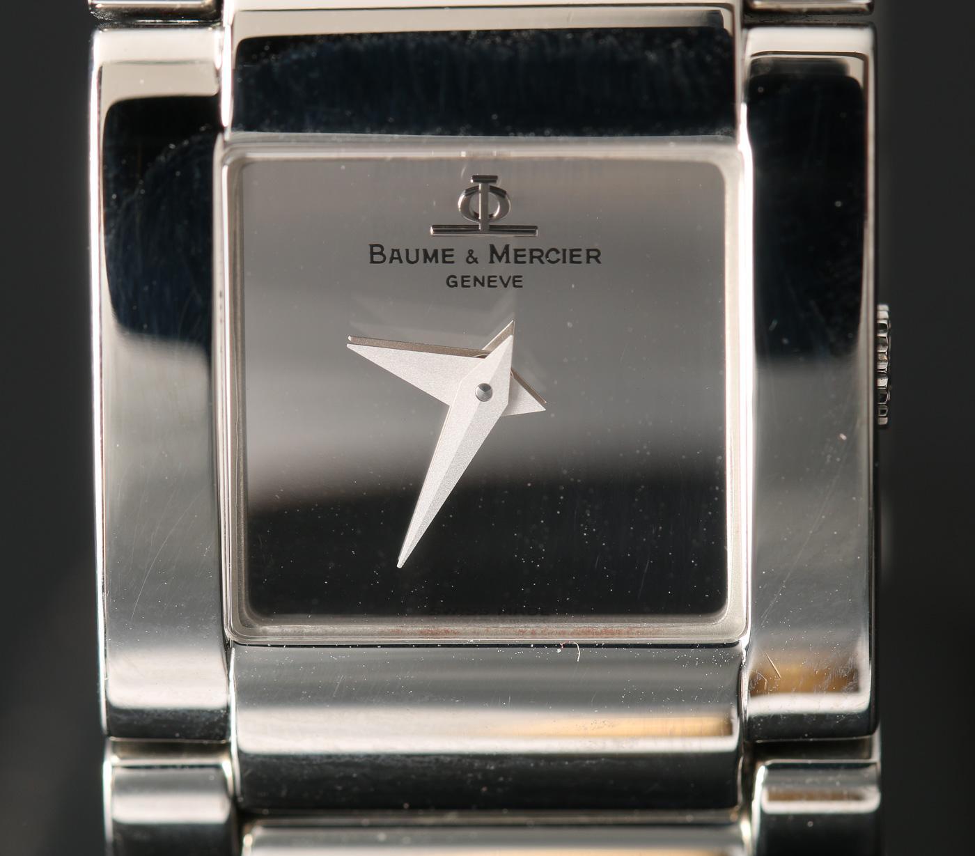 Baume & Mercier, damearmbåndsur - Baume & Mercier, ref. MV045219, damearmbåndsur i urkasse af stål, urskive med logo og to visere. Uret har schweizisk quartzværk, integreret lænke i stål med foldespænde. Bredde: 22 mm (ekskl. krone). Bagkasse stemplet 4062042. Der medfølger...
