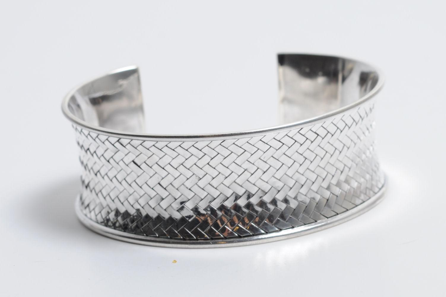 Åben armring af sterling sølv - flet - Åben armring udført i sterling sølv, front med fletdekor. Omkreds ca. 25 cm. Bredde ca. 21 mm. Vægt ca. 38 gram