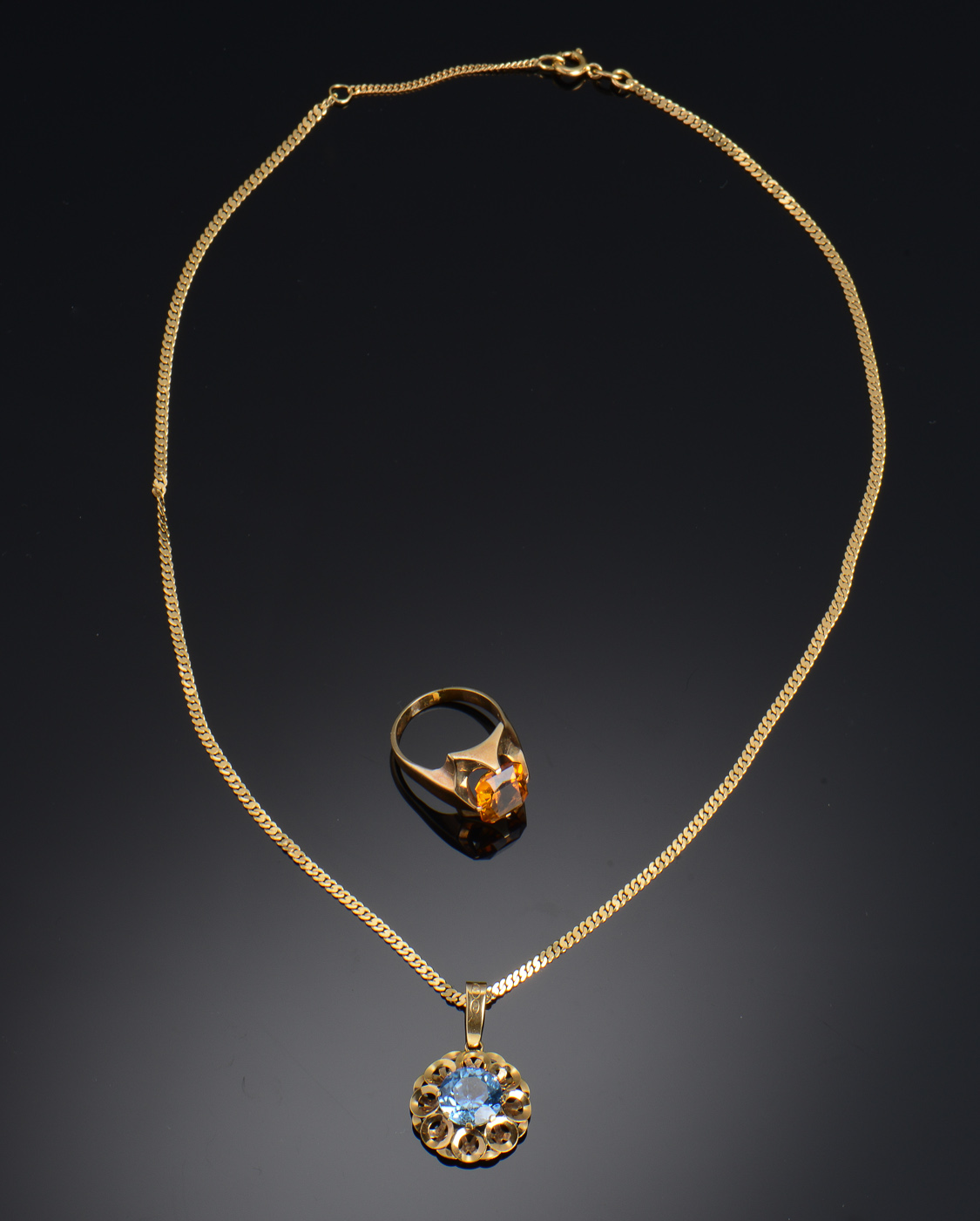 Ring samt halskæde af guld - Ring af 14 kt guld, prydet med en citrin, bredde af front ca 15 mm Ringstr. 54 Endvidere vedhæng af 18 kt guld, prydet med en lyseblå syntetisk spinel. Mål af vedhæng ca ø 1,9 cm, dertil panser halskæde af 18 kt guld. Samlet vægt ca 16 gr
