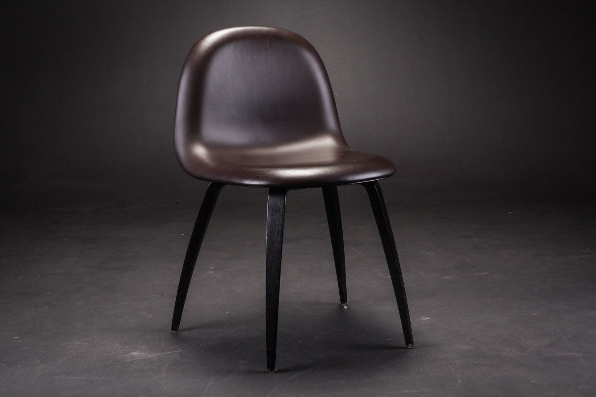 Gubi Chair. Stol, model 52 - Gubi Chair. Stol, model 52 med skal og stel af formspændt, sortlaseret bøg, forsidepolstret med dybbrunt læder. H. 80 B. 50 Sh. 46 cm. Design by Komplot. Fremstillet for Gubi 2012. Fremstår med brugsspor i form af ganske let patineret læder,...