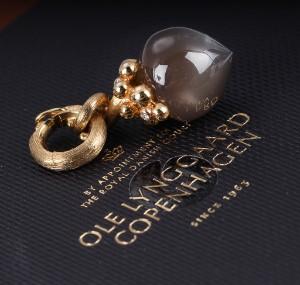 Ole Lynggaard. Stor Filigran Dew Drops-charm i 18 kt. guld med månesten - Dk, Vejle, Dandyvej - Ole Lynggaard. Stor 'Filigran Dew Drops'-charm i 18 kt. guld med cabochonsleben grå månesten, top prydet med tre brillantslebne diamanter på i alt 0.03 ct. Farve: Top Wesselton (G). Klarhed: VS. Art. nr. A 2635-401. Vægt ca. 6,3  - Dk, Vejle, Dandyvej