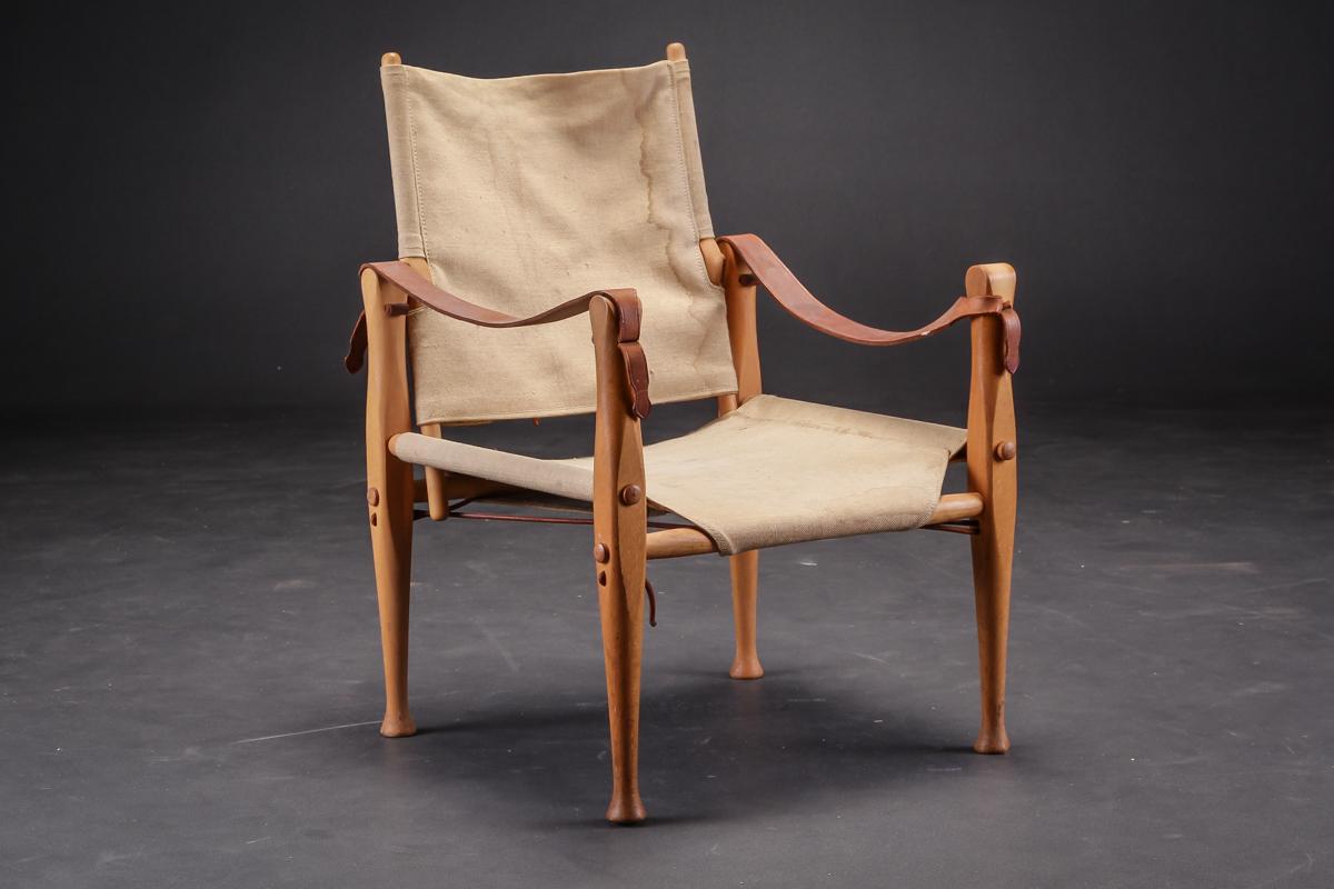 Axel Thygesen. Barne safaristol af bøgetræ, prototype - Axel Thygesen 1927-1976. Barne safaristol af bøgetræ, sæde og ryg udspændt med kernelæder, armlæn af kernelæder. Stolen er en prototype, og aldrig sat i produktion. Fremstår med brugsspor, skjolder på betræk samt afslag på forreste venstre...