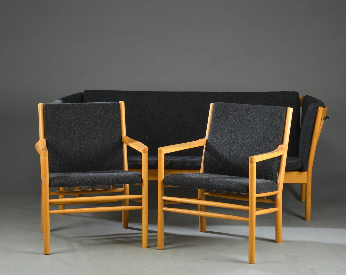 Tremmesofa samt par lænestole med stel i massiv eg - Tremmesofa samt to lænestole med stel i massiv eg, løse hynder betrukket med mørkegrå uld. Sofa H. 79. B. 190 cm. Stole B. 62 cm. Fremstår med brugsspor, ridser og mærker