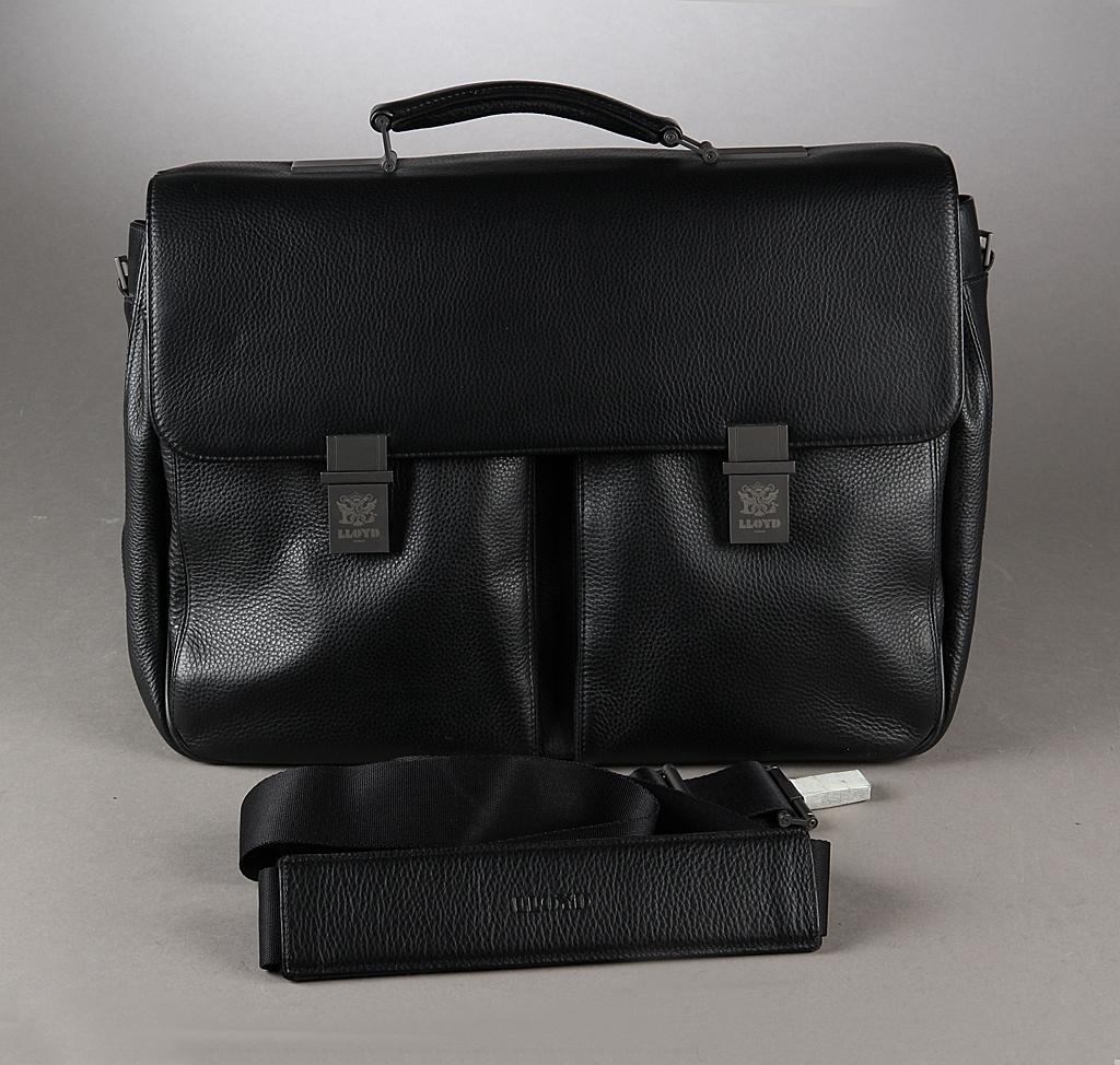 Lloyd. Businesstaske i sort læder - Lloyd. Businesstaske i sort læder med hank og skulderem, spændelukke, to lommer på front, indvendig tre rum, to lynlåsrum og 3 små lommer, bagside med lynlåsrum. Mål 45 x 32 x 14 cm. Fremstår ubrugt