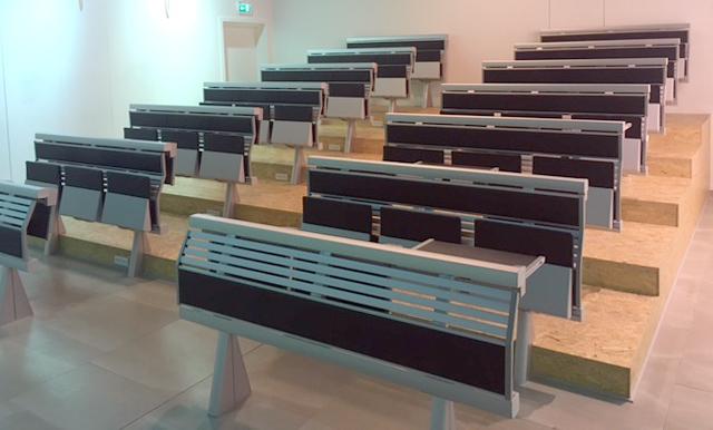 Auditoriestole 36 siddepladser - Auditoriestole. 36 siddepladser fordelt på 12 moduler samt 2 stk. front moduler fremstillet af metal/træ. Monteret med siddepladser betrukket med sort læder samt optræks bordplader af træ. H. 100 cm., B.154 cm. Fremstår med alm. brugsspor