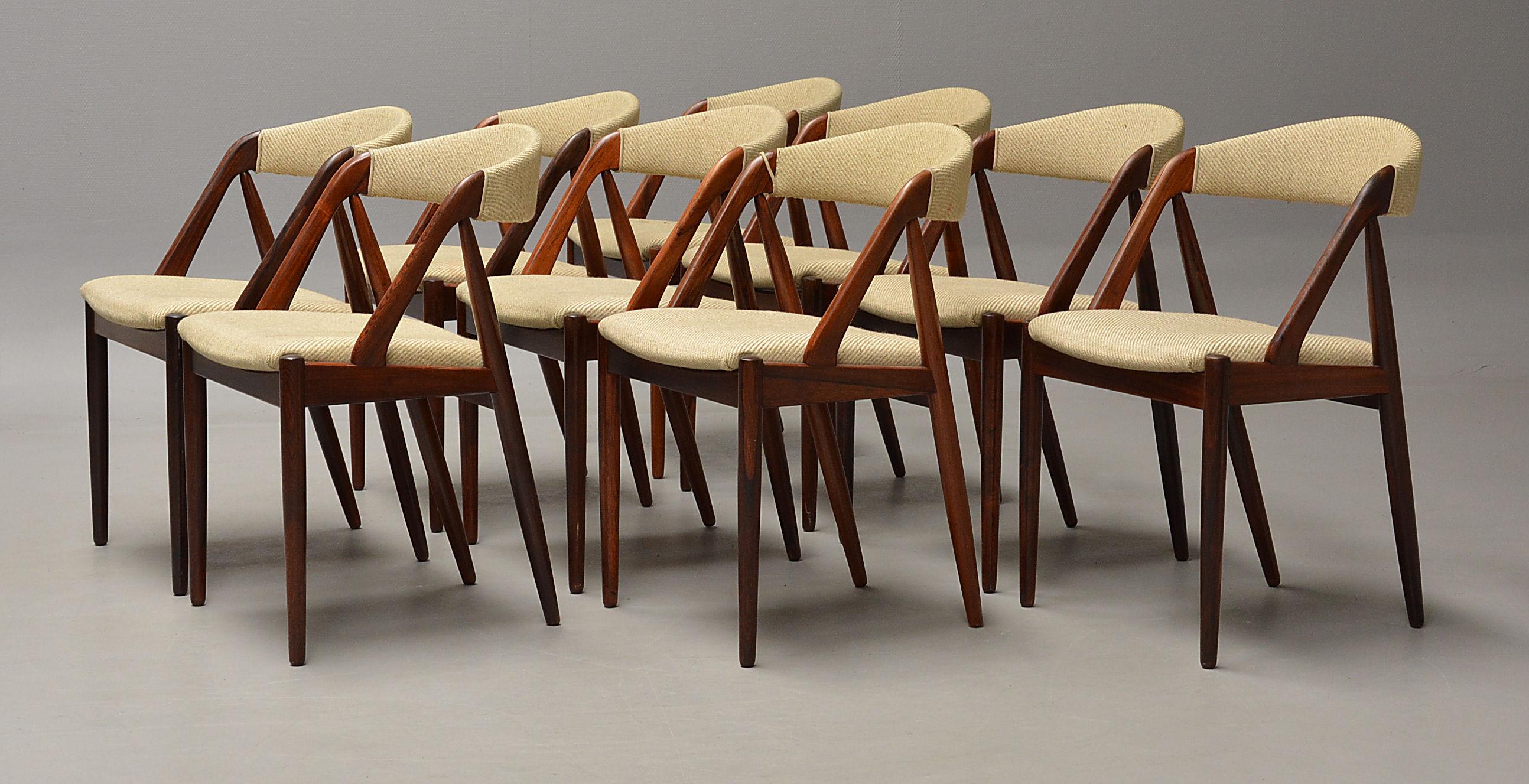 Kai Kristiansen. Sæt på ni stole i palisander - Kai Kristiansen. Sæt på ni stole af massiv palisander betrukket med lyst møbelstof. H. 44/75 cm. Fremstår med brugsspor, sæder med nogle pletter, én stol med løs kæde ved armlæn