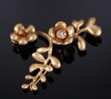Ole Lynggaard. Blomstervedhæng / -lås i form af blomsterranke af 18 kt guld med brillanter