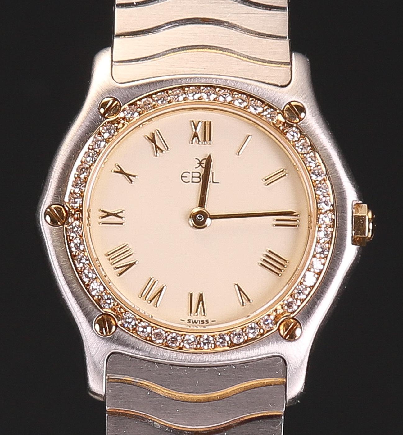 Ebel damearmbåndsur af guld 18 kt. og stål med diamanter - Ebel damearmbåndsur af guld 18 kt. og stål med quartz urværk. Urskive mrk. Ebel med timeindikationer i form af romertal. Krans originalt monteret med 39 diamanter i VVS1 kvalitet. Bagkasse mærket med nummer 12665353, 181930X. Integreret lænke af...