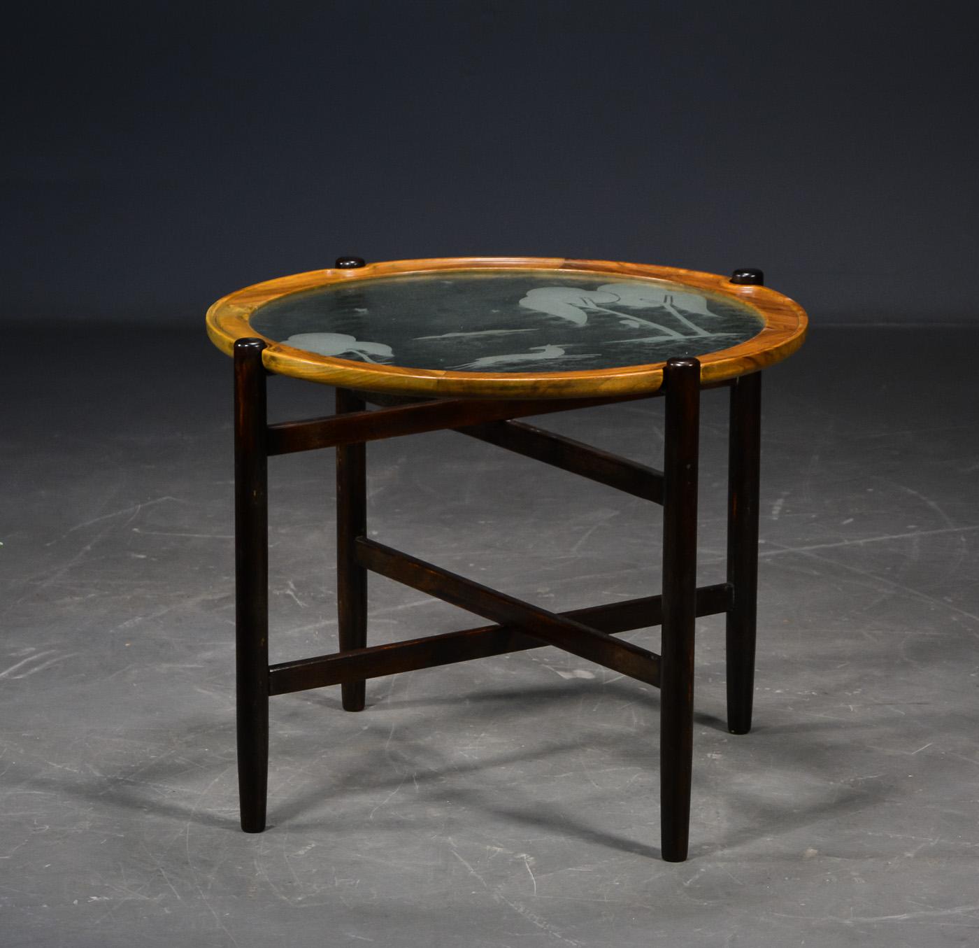 Art Deco sofabord med glasplade, ca. 1930 - Art Deco sofabord med glasplade, ca. 1930. Mørkbejdset foldeunderstel, bordpladeramme af massiv valnød. Glasplade med ætsede hjorte- og træmotiver. Alm. brugs- og alderspræg. Enkelte afslag på rammekant. H. 49. Ø. plade 60 cm