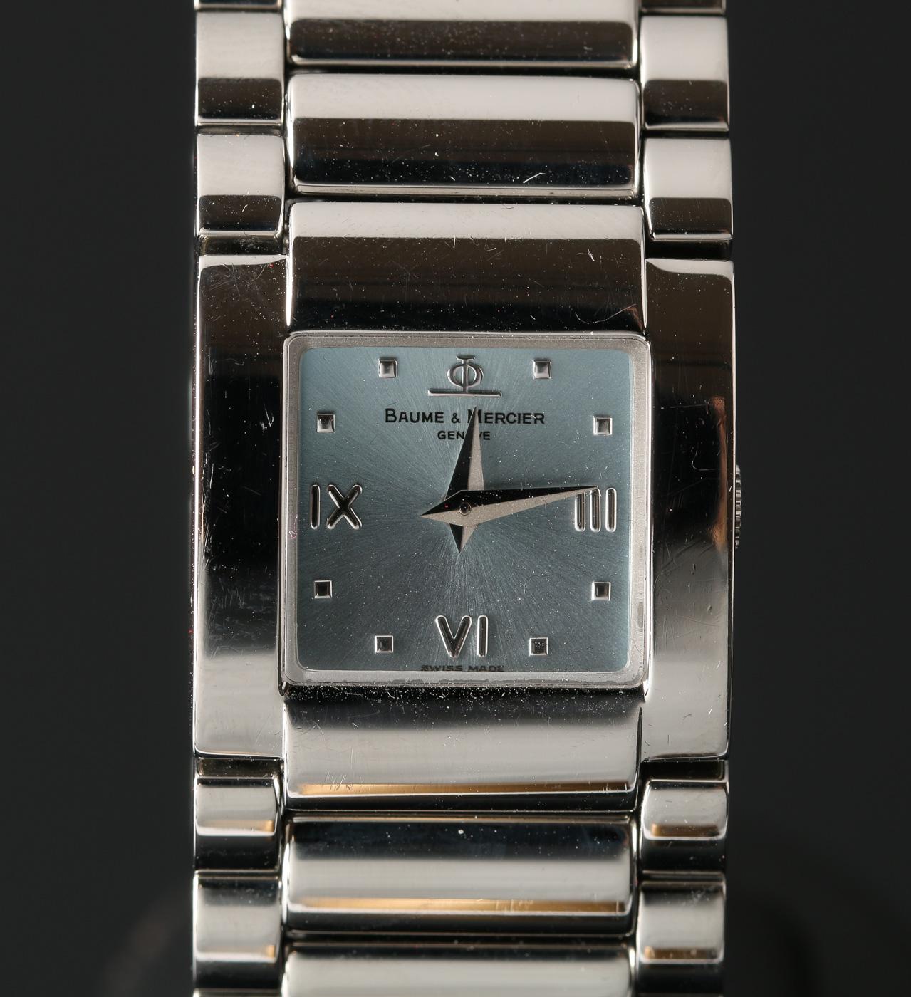 Baume & Mercier, damearmbåndsur - Baume & Mercier, ref. MV045219, damearmbåndsur i urkasse af stål med lys skive med logo, timemarkeringer, to visere. Uret har schweizisk quartzværk, integreret lænke i stål med foldespænde. Bredde: 22 mm (ekskl. krone). Bagkasse stemplet...