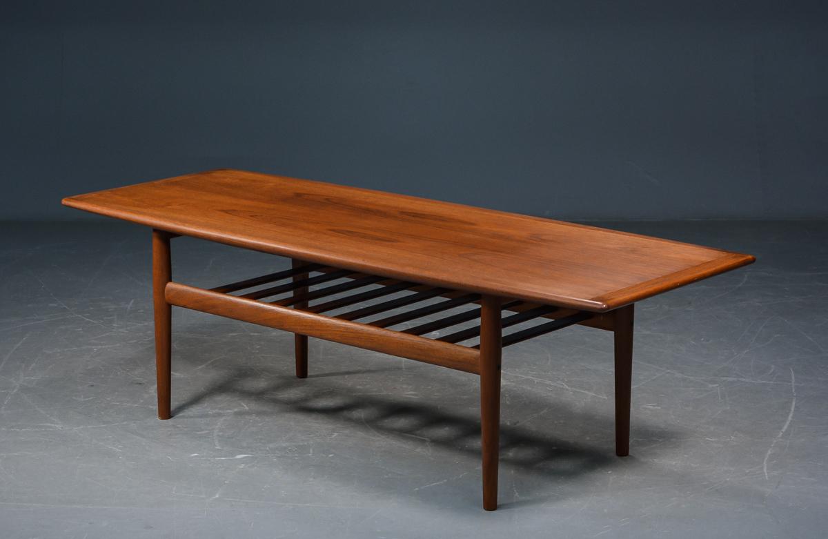 Grethe Jalk - Sofabord af teak - Grethe Jalk, sofabord af teak med underliggende tremmehylde, tilspidsede ben. Mål: 160x60 cm. H. 50 cm