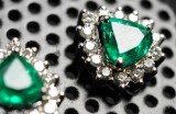 A pair of earrings with emeralds and diamonds