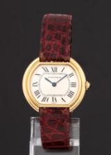 Cartier 'Tonneau'. Dameur i 18 kt. guld prydet med safir, 1990´erne