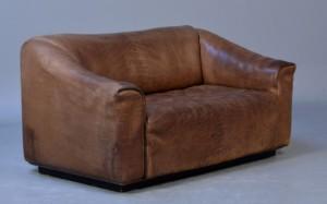 De Sede. 2-pers. sofa med sort læder, DS-47 - Dk, Kolding, Trianglen - De Sede. To-personers sofa overpolstret med patineret, sort kraftigt tyre / 'Neck-læder'. Siddeflade med udtræk for bedre komfort. H. 70 cm. L. 140 cm. Fremstillet hos De Sede, Schweiz. Model DS 47. - Dk, Kolding, Trianglen