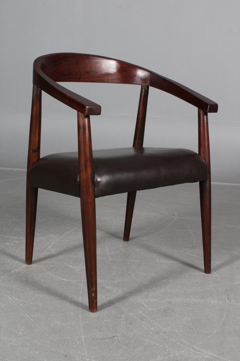 Armstol, kopstykke af teak. Læder - Armstol. Udført i bejdset træ, kopstykke af bejdset teak. Sæde i mørkebrunt læder, dækfarvet. H. 78 cm. SH. 46 cm. B. 58 cm