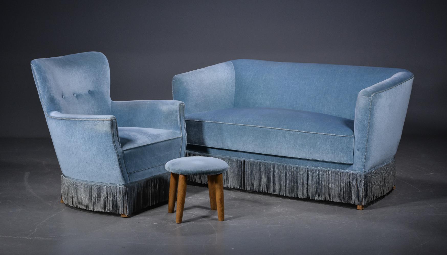 Sofa, stol, samt skammel med blå velour - Sofa, stol, samt skammel med ben af egetræ, betrukket med med blå velour, syet med keder og kantet med frynser. Stol knapsyet i ryg. Mål: Længde på sofa er ca. 130 cm. D. 80 cm. Sædeh. 45 cm. Stol: B. 75 cm. Sædehøjde 45 cm. Mål på skammel:...