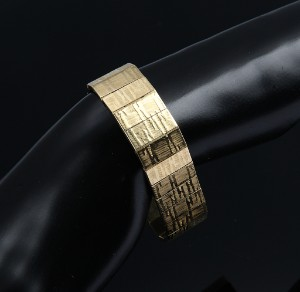 Bred armlænke af 18 kt. guld med satineret overflade, ca. 1960'erne - Dk, Vejle, Dandyvej - Bred armlænke af 18 kt. guld med satineret overflade, monteret med kasselås med dobbelte sikkerhedshaspe, udført ca. 1960'erne. L. 18,5 cm. B. 18 mm. Vægt: ca. 55,9 gr. Fremstår med brugsspor. - Dk, Vejle, Dandyvej