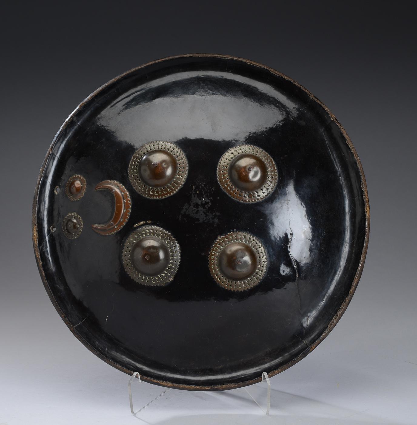 Indo-persisk skjold, 1800-tallets første halvdel - Indo-persisk skjold af lakeret papmaché, prydet med bronzer. Greb fastgjort med mønter dateret 1835. Ø 36 cm. Aldersrelaterede brugsspor