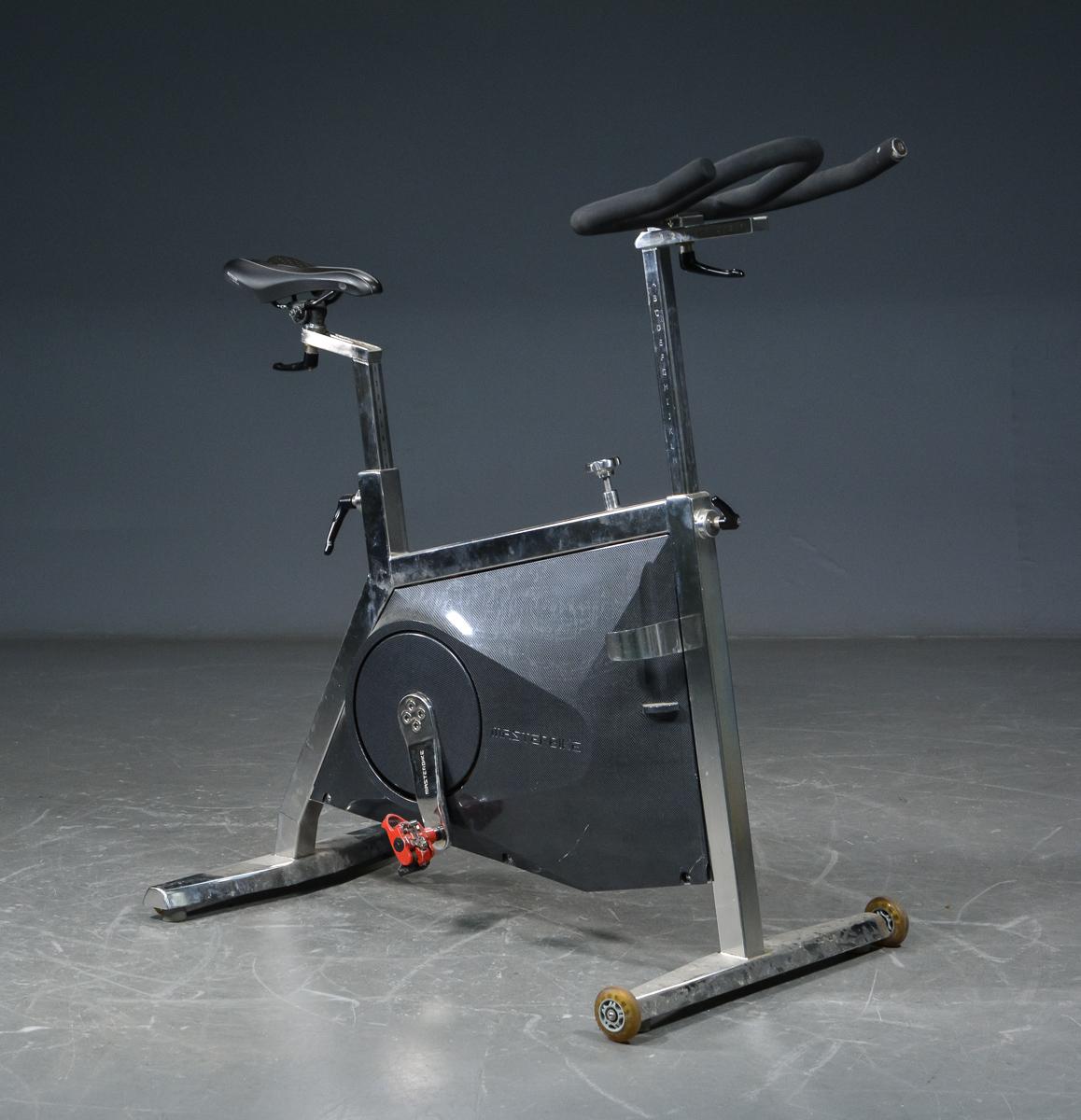 Masterbike, professionel spinningcykel - Masterbike, professionel spinningcykel i rustfri stål, monteret med Kettler sadel. Brugsspor samt antiseptisk gummi med slitage