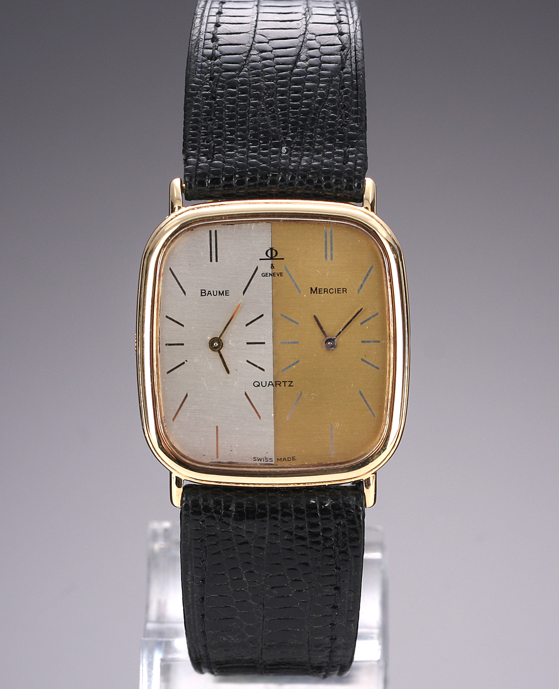 Baume & Mercier Dual Time. Herreur i 18 kt. guld two-tone skive, 1970-80erne - Vintage herrearmbåndsur fra Baume & Mercier, model Dual Time, i urkasse af 18 kt. guld, two-tone skive med stregindeks, dual time-funktion, mineralglas, monteret med original læderrem med forgyldt spænde, quartz urværk. Mål: 29 x 34,9 mm....