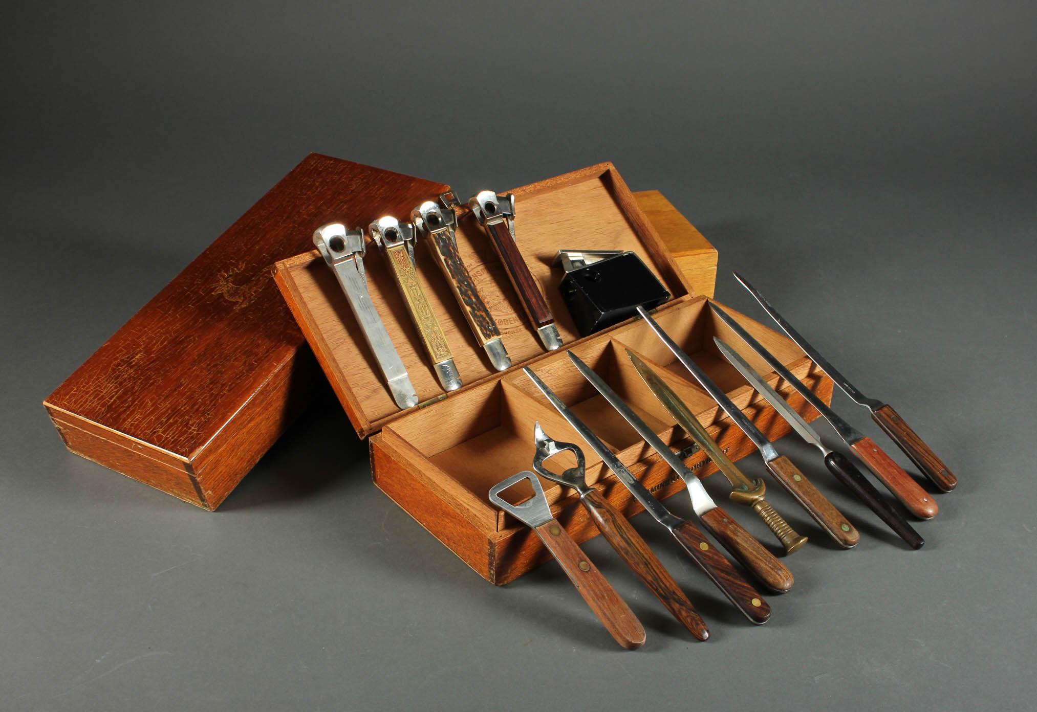 Cigaræsker samt brevknive - Cigaræsker af lakeret træ med cigarklippere samt seks brevknive med skæfter af bl.a. palisander, én af messing samt to oplukkere. H. 6 L. 34 B. 15 cm. L. 14 - 25 cm. Fremstår med brugsspor