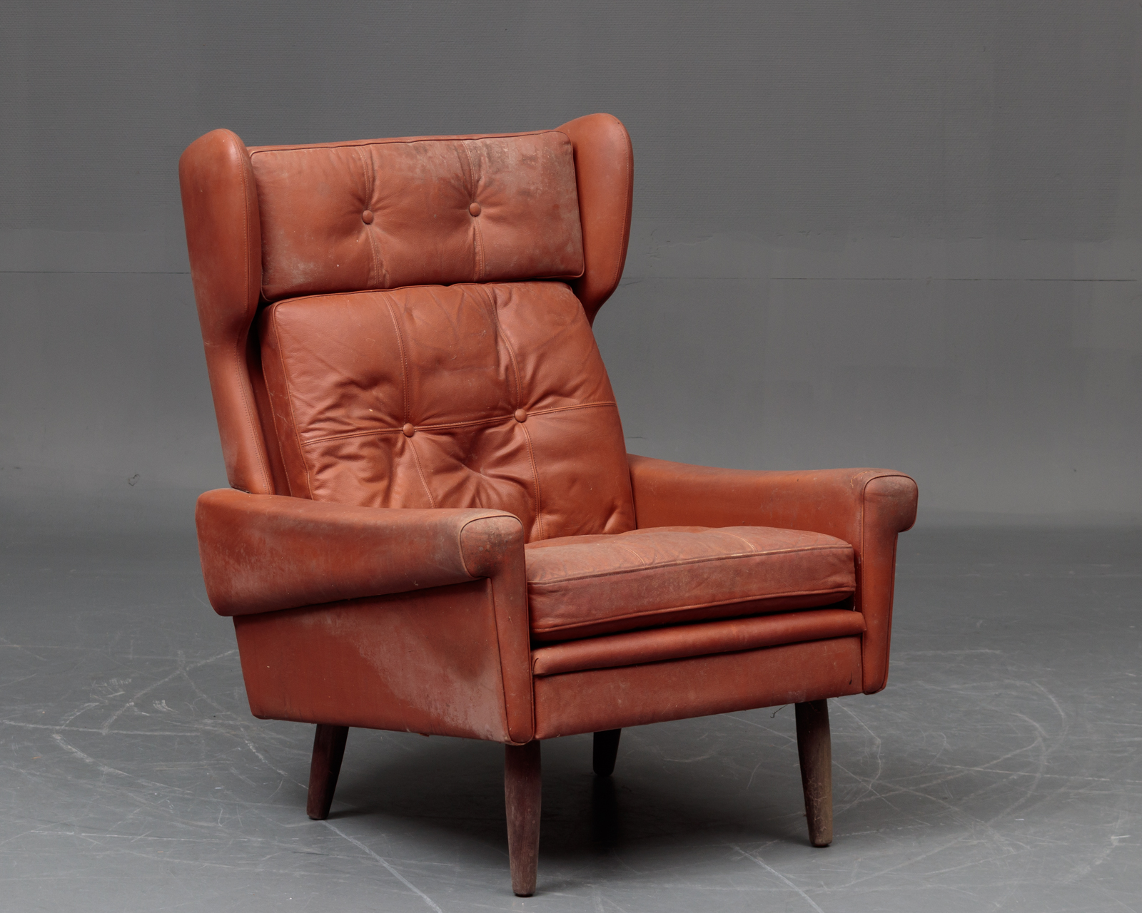 Svend Skipper: Øreklapstol - Svend Skipper: Øreklapstol beklædt med cognacfarvet læder. H 97 cm, SH 44 cm. Fremstår med opbevaringsspor og snavs