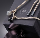 Ole Lynggaard. Two 'Dew Drop' charms, 18 kt. white gold with moonstone and onyx. silk cord with sterling silver ends (3)