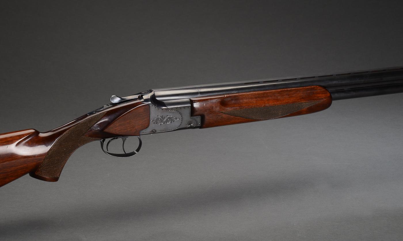 Winchester Model 400 o/u haglgevær kal. 12/70 - Winchester Model 400 o/u haglgevær Ejektor Singletrigger Løbsvælger kaliber 12-70. Totallængde: 113 cm. Løbslængde: 71 cm. 37 cm kolbe med skarpe netskæringer, rosette-graveringer, manuel sikring. Serienummer K319156. Kolbehælen fremstår med...