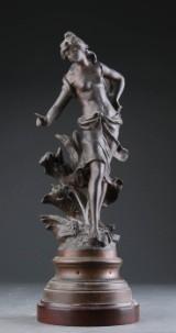 Figur af patineret metal i form af stående kvinde
