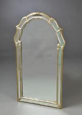 Spejl i forsølvet ramme med halvrund top dekoreret med bladværk.