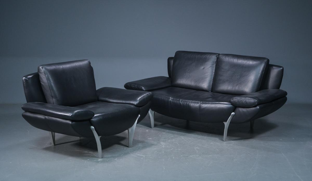 Sofa samt lænestol, sort læder, Italiensk stil - Sofa samt lænestol med ben af metal, betrukket med sort læder, Italiensk stil, H. 76/76 cm. L. 120/175 cm. B. 80 cm. Sædehøjde 45 cm. Fremstår med brugsspor, slid på læder samt lænestol med ridser/kradsmærker på sæde