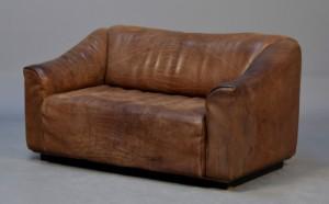De Sede. To-pers. sofa med sort læder, DS-47 - Dk, Kolding, Trianglen - De Sede. To-personers sofa overpolstret med patineret, kraftigt tyre / 'Neck-læder'. Siddeflade med udtræk for bedre komfort. H. 70 cm. L. 140 cm. Fremstillet hos De Sede, Schweiz. Model DS 47. Fremstår med afslag på sokkel. - Dk, Kolding, Trianglen