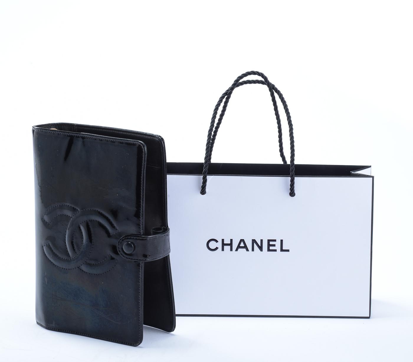 Chanel, kalender - Chanel, kalender udført af sort laklæder. Indvendigt med plads til planner samt par sidelommer. 18,5 cm x 13 cm. Udført i perioden 1996-1997