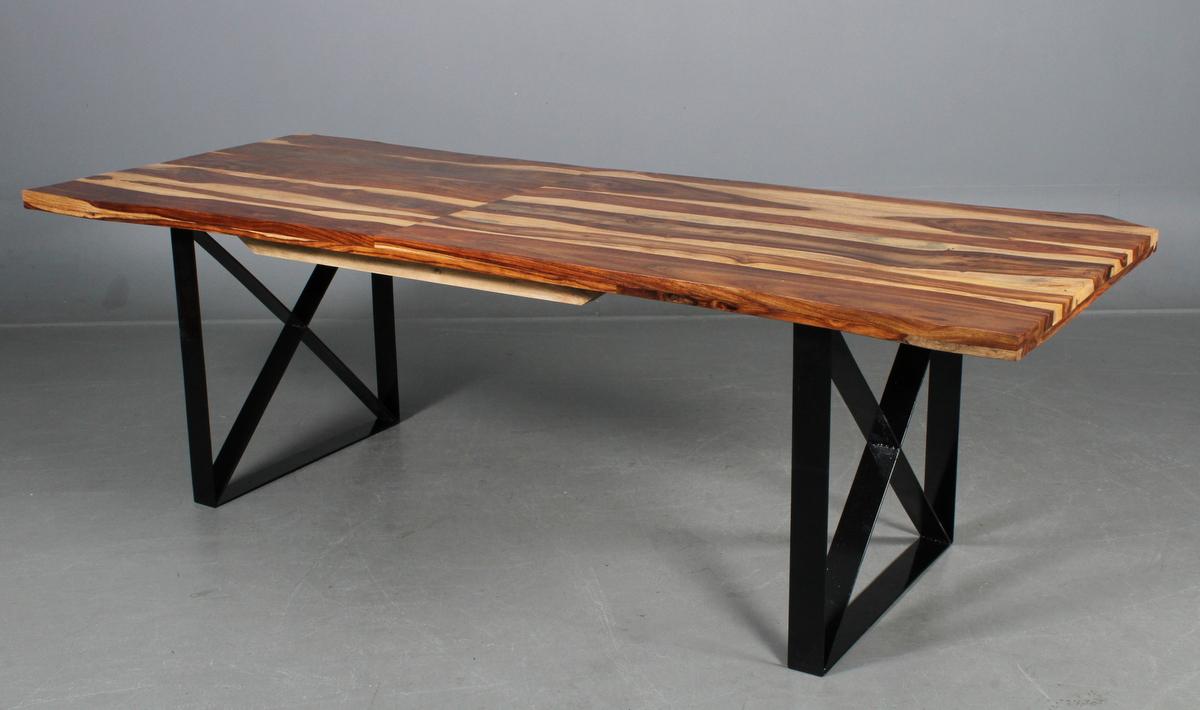 Rustikt plankebord. Sheesham - Rustikt plankebord. Udført i eksotisk hårdttræ, sheesham. Sort lakerede ben med tværstiver. L. 250 cm. B. 100-89 cm. H. 80 cm. Fremstår med enkelt trykmærke på underside kant, svejsning gået i ene tværstiver samt bordet rokker. Ene ende har...