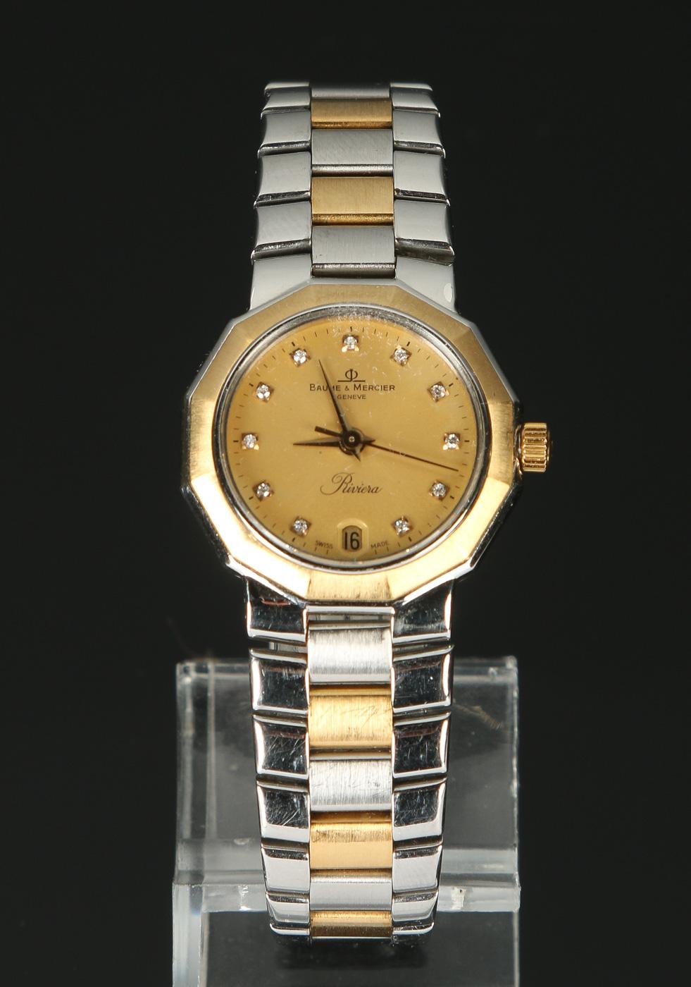Baume & Mercier Riviera, damearmbåndsur med diamanter - Baume & Mercier model Riviera. Damearmbåndsur i urkasse af stål med krans og krone af 18 kt guld. Urskive med logo, tre visere samt dato. Safirglas. Uret har quartz urværk. Integreret Baume & Mercier lænke af stål og 18 kt guld, monteret med...
