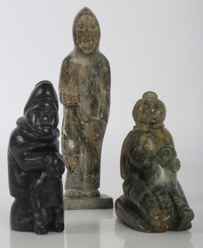 Grønlandica. Tre figurer i udskåret fedtsten. Alle tre sign - Grønlandica. Tre figurer i udskåret fedtsten. Alle tre sign. H. hhv. 10-12-18 cm. To stk. sign. R.B, samt et stk E.M. Største med reparation