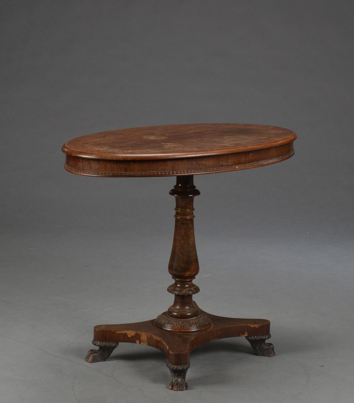 Sofabord af mahogni, 1800-tallets slutning - Salonbord af massivt mahogny, oval plade, balusterformet søjle med udskæringer, afsluttet på løvefødder. 1800tallet. H. 74 L. 90 D. 60 cm. Fremstår med brugsspor og varmeskjold på plade