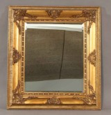 Spejl i ramme af guldbemalet træ.