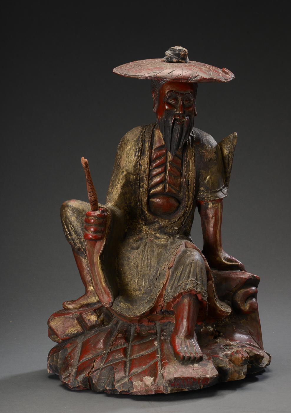 Orientalsk figur af udskåret træ - Orientalsk figur af udskåret og bemalet træ, i form af fisker. H. 61 cm. 1900-tallet. Fremstår med manglende fiskestang, fisk med mærker/afslag