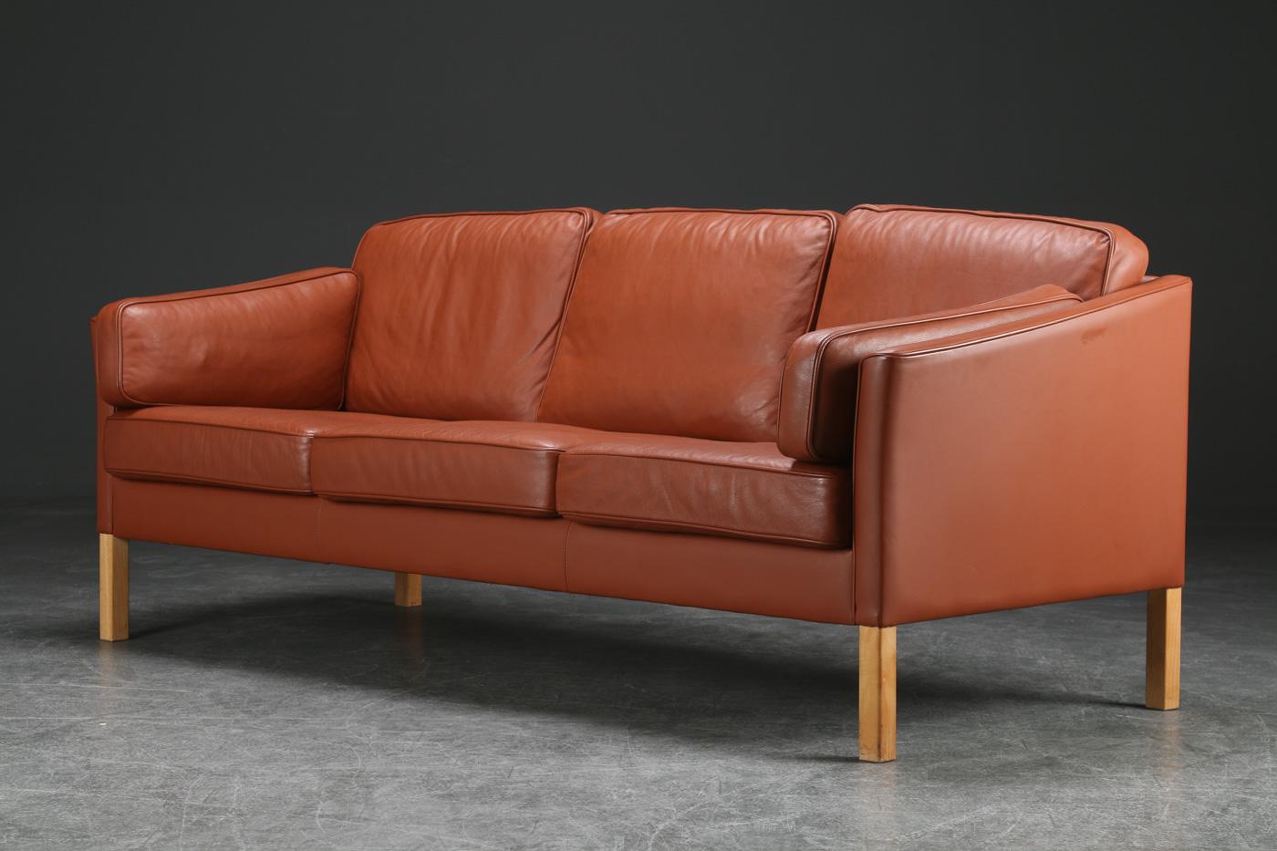 Stouby. Tre-personers sofa, læder - Stouby. Tre-personers sofa, hynder, sider og ryg, betrukket med brunt læder, ben af eg. L. 200, sædehøjde 42 cm. Lette brugsspor