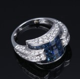 An English sapphire and diamond ring, 18 kt. white gold with invisible setting. London 2000