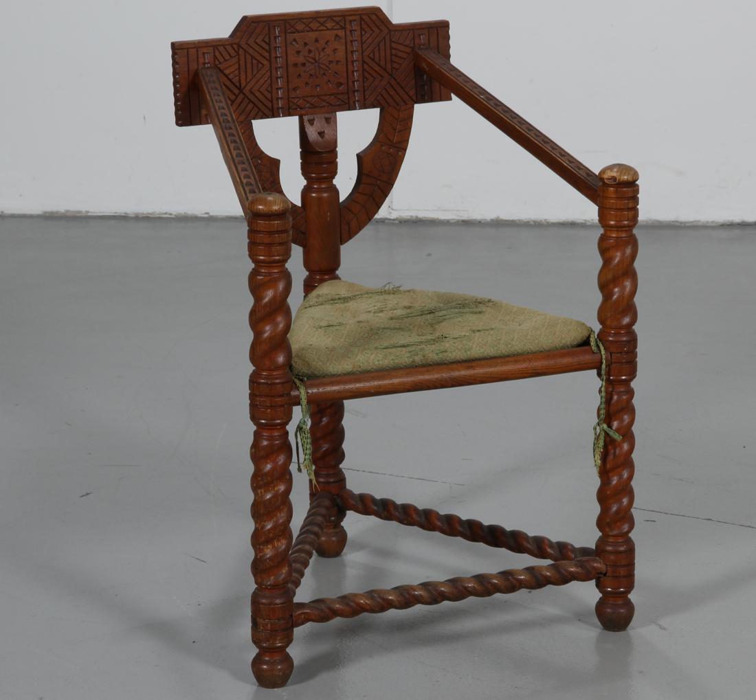 Almue hjørnestol af lakeret egetræ, 1900-tallets første halvdel - Almue hjørnestol af lakeret egetræ, prydet med skæringer, løs hynde betrukket med grønt stof, 1900-tallets første halvdel. H. 87/46 cm. Fremstår med brugsspor, gennemslidt hynde