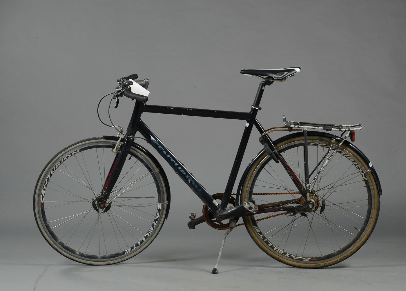 Centurion, herrecykel. 5787 - Herrecykel fra Centurion med syv gear. Fremstår med brugsspor, rust på kæde og skruer. Låst. Stel str. 58cm. Stel nr. WAK38535D Auktioner over hittegods, cykler, og koster fra Københavns Politi Se alle auktionerne her OBS! OBS! Venligst vær...