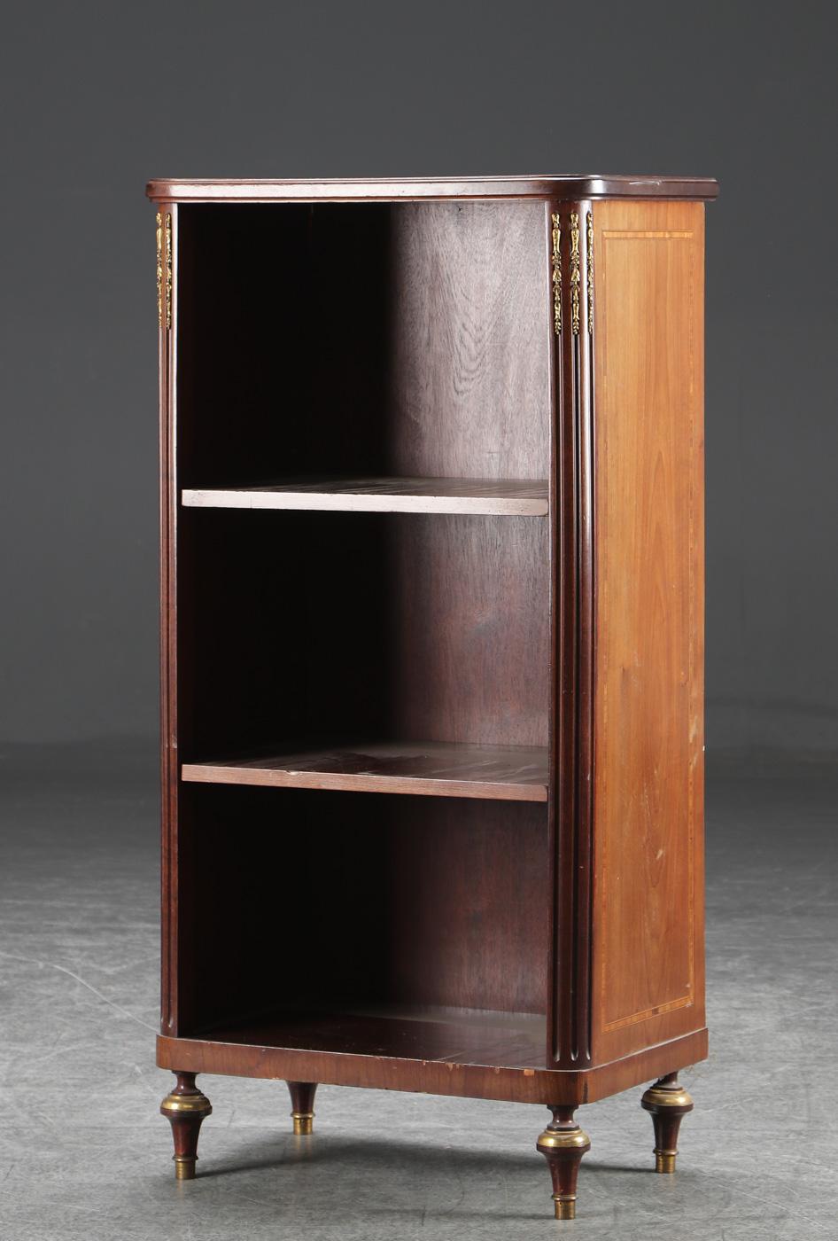 Reol af mahogni, rokokoform, 1900-tallets 1. halvdel - Rokokoform reol af mahogni, prydet med beslag af bronze. 1900-tallets første halvdel. Fremstår med alders- og brugsrelateret slitage. H. 105 cm B. 53 cm D. 33 cm